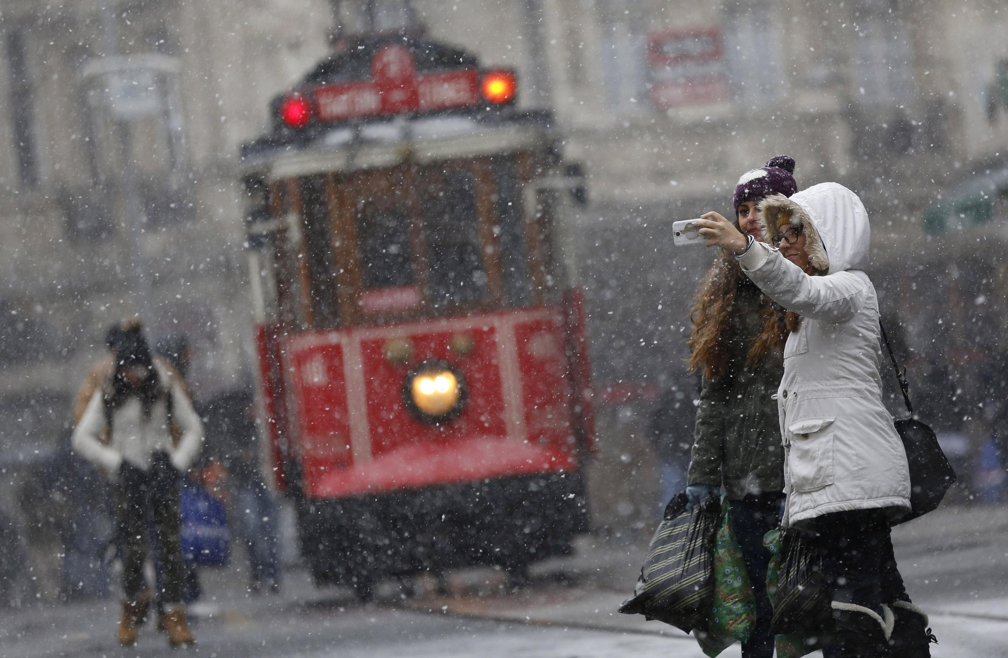 "Pedestrians, with a vintage tram in the background, take a ""selfie"" as snow falls at the main shopping street of Istiklal in central Istanbul, in this January 6, 2015 file photo. REUTERS/Murad Sezer/Files (TURKEY - Tags: ENVIRONMENT SOCIETY) ATTENTION EDITORS - THIS PICTURE IS PART OF THE PACKAGE ""THE SELFIE PHENOMENON"". TO FIND ALL 19 IMAGES SEARCH 'SELFIE'"